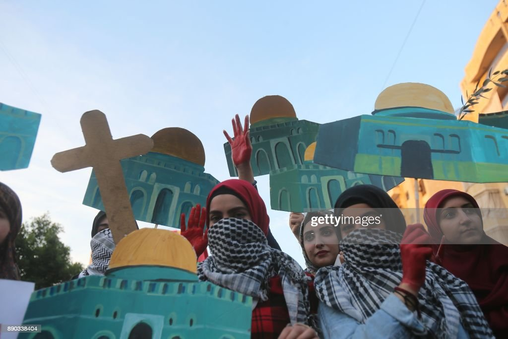 Supporters of Lebanon's Hezbollah Shiite movement hold up models of Jerusalem's Dome of the Rock mosque and a cross as they march through the Lebanese capital Beirut on December 11, 2017 in protest against the US president's controversial recognition of Jerusalem as Israel's capital. /