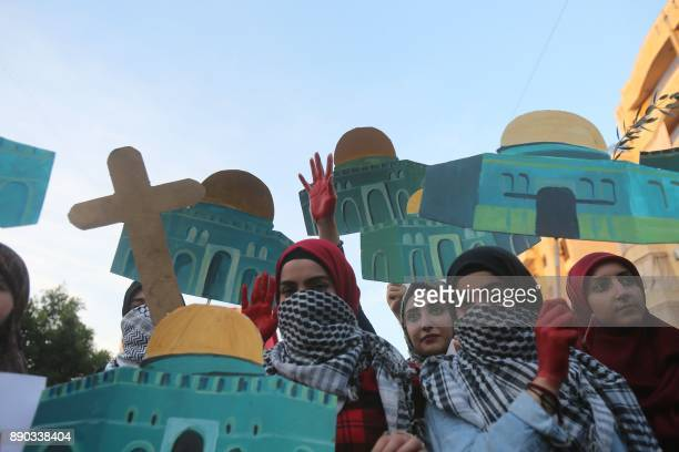 Supporters of Lebanon's Hezbollah Shiite movement hold up models of Jerusalem's Dome of the Rock mosque and a cross as they march through the...