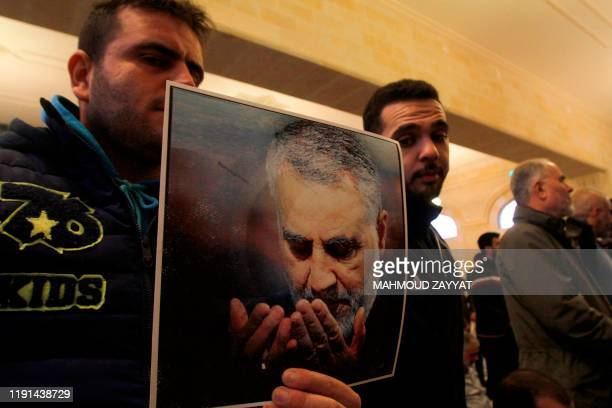 Supporters of Lebanon's Muslim Shiite group Hezbollah hold a picture of slain Iranian Revolutionary Guards Major General Qasem Soleimani who was...