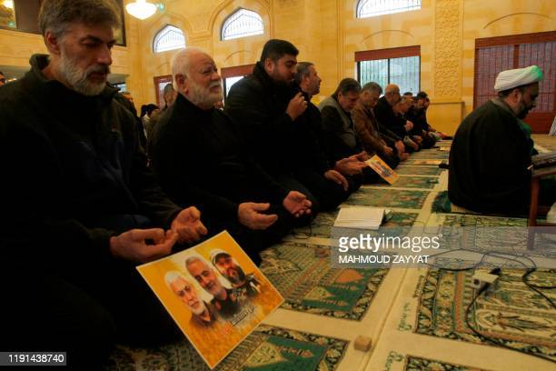 Supporters of Lebanon's Muslim Shiite group Hezbollah perform a mourning prayer for slain Iranian Revolutionary Guards Major General Qasem Soleimani...