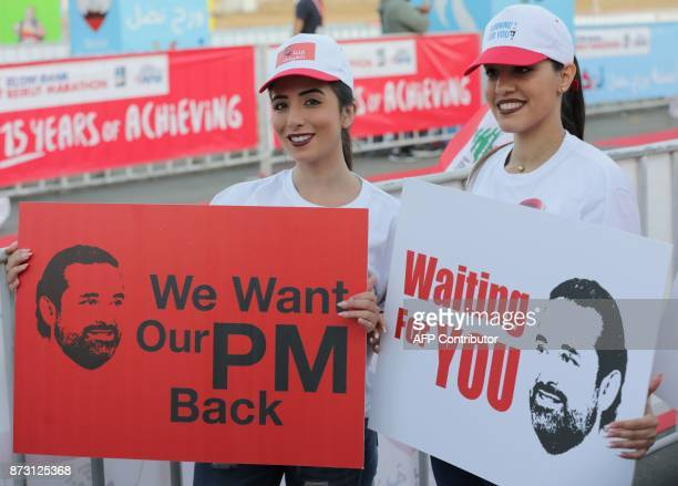 Supporters of Lebanon's resigned prime minister Saad Hariri hold up placards demanding his return from Saudi Arabia on the starting line of Beirut's...