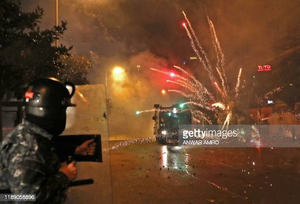 TOPSHOT Supporters of Lebanon's Shiite Hezbollah and Amal groups hurl fireworks at security forces early on December 17 2019 in central Beirut...