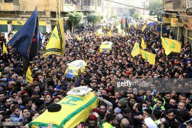 Supporters of Lebanon's Shiite Hezbollah movement carry coffins of the group's fighters killed in Syria, during their funeral procession in a suburb...