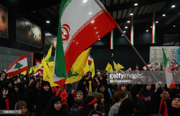 Supporters of Lebanon's Shiite movement Hezbollah wave national Iranian as well as the movement's yellow flag during celebrations marking the 40th...