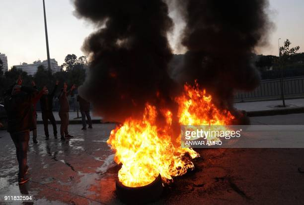Supporters of Lebanon's Shiite Muslim parliament speaker flash the Vsign as they burn tyres to block a main road in Beirut on January 29 following a...