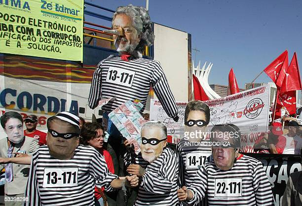 Supporters of leftist Brazilian parties carry 17 August 2005 in Brasilia dummies of President Luiz Inacio Lula da Silva with Pinochio's nose and some...