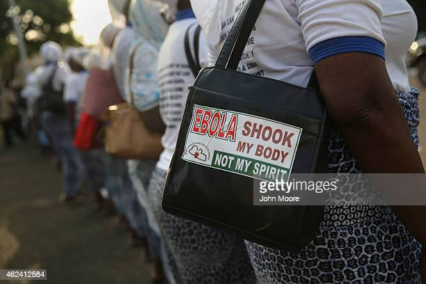 Supporters of Liberian President Ellen Johnson Sirleaf wait for her to emerge from the national legislature building on January 26 2015 in Monrovia...