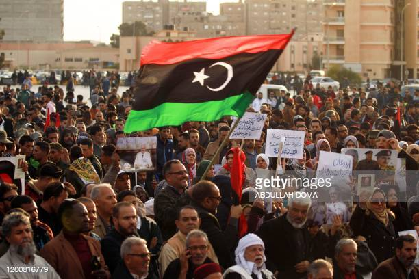 Supporters of Libyan military strongman Khalika Haftar wave a national flag as they take part in a demonstration in the coastal city of Benghazi in...