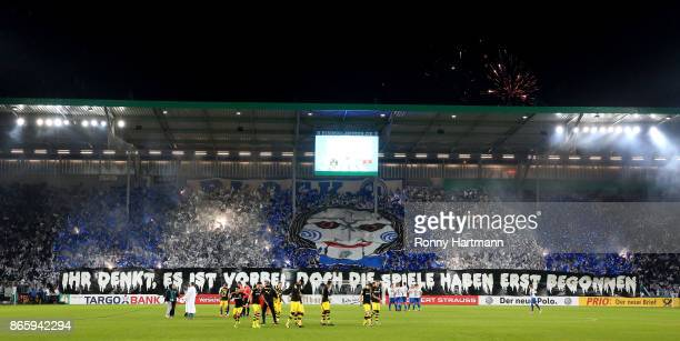 Supporters of Magdeburg handle with pyrotechnic prior to the DFB Cup match between 1 FC Magdeburg and Borussia Dortmund at MDCCArena on October 24...