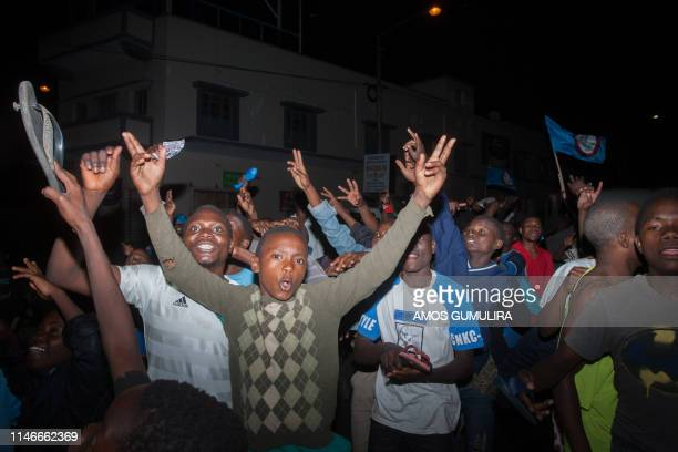Supporters of Malawi's ruling Democratic Progressive Party celebrate in the streets of Blantyre on May 27 following President Peter Mutharika's...