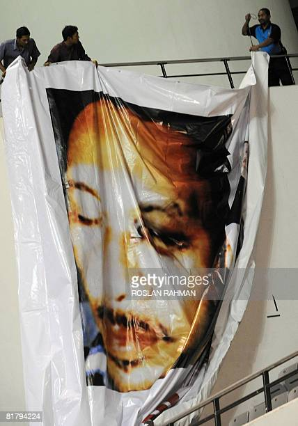 Supporters of Malaysian opposition leader Anwar Ibrahim hang a poster of him at a rally in Selangor state on July 1 2008 showing a black eye...