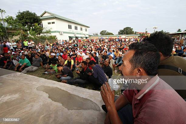 Supporters of Malaysia's opposition leader Anwar Ibrahim listen to his speech during Free Anwar tour in Kuantan some 253 kilometers from Kuala Lumpur...