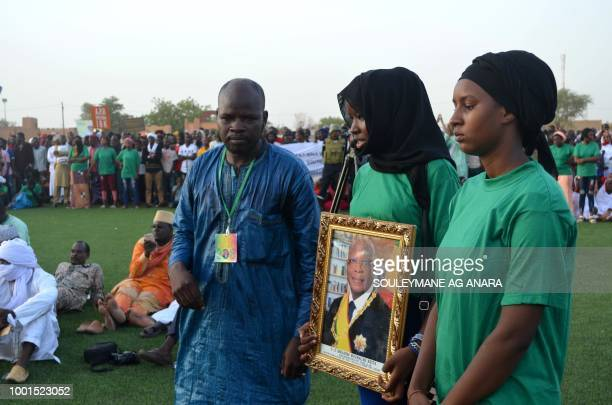 TOPSHOT Supporters of Malian incumbent president Ibrahim Boubacar Keita wait at the Gao stadium on July 18 2018 for a presidential campaign rally