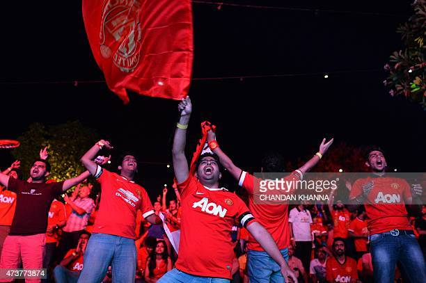 Supporters of Manchester United cheer during the English Premier League football match between Manchester United and Arsenal in New Delhi on May 17...