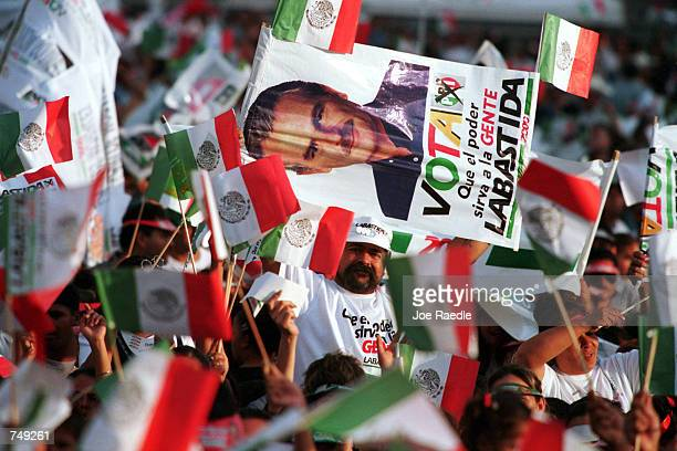 Supporters of Mexican presidential candidate Francisco Labastida wave flags and hold campaign posters during a concert by international music star...