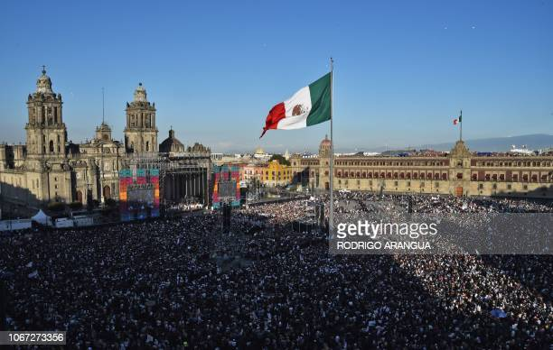 Supporters of Mexico's new President Andres Manuel Lopez Obrador watch the inauguration ceremony on a huge screen at the Zocalo square in Mexico City...