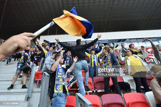 Supporters of Mezokovesd cheer their team during the national championship's football match between DVTK and Mezokovesd in the DVTK stadium of...