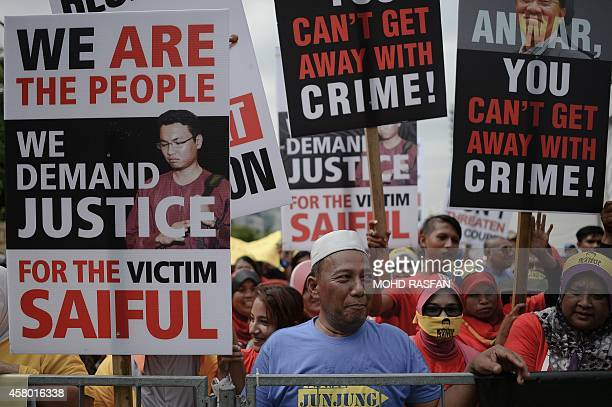 Supporters of Mohamad Saiful Bukhari Azlan hold placards and shout slogans against Malaysian opposition leader Anwar Ibrahim outside the court of...