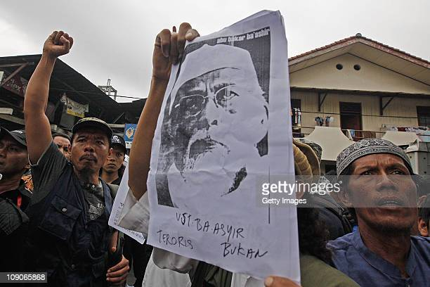 Supporters of Muslim cleric Abu Bakar Bashir shout slogans and hold signs to show their support as he appears in court on February 14 2011 in Jakarta...