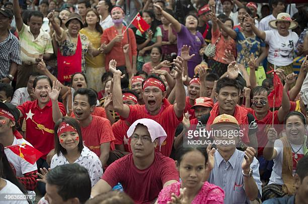 Supporters of Myanmar opposition leader Aung San Suu Kyi celebrate as they hear the first official results of the elections on a giant screen outside...