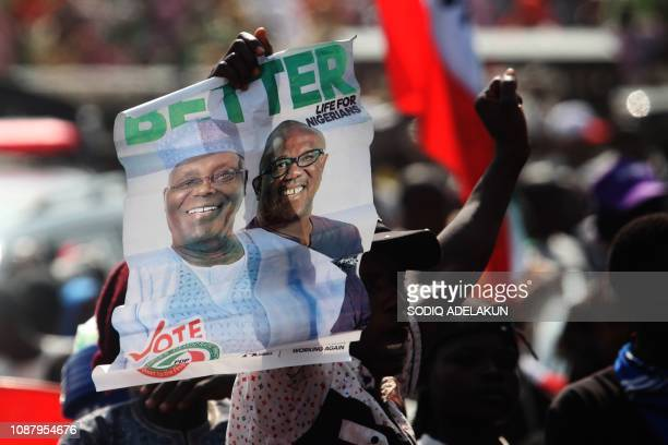 TOPSHOT Supporters of Nigerian opposition presidential candidate of the People's Democratic Party Atiku Abubakar hold his portrait during a campaign...