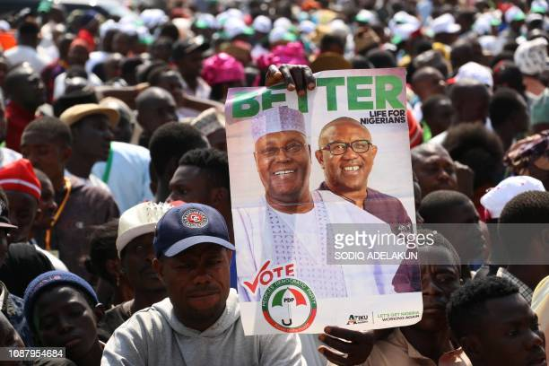 Supporters of Nigerian opposition presidential candidate of the People's Democratic Party Atiku Abubakar hold his portrait during a campaign rally at...