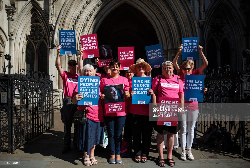 Supporters of Noel Conway from the campaign group Dignity in Dying pose with placards outside the Royal Courts of Justice, Strand on July 17, 2017 in London, England. Mr Conway, 67, who is terminally ill with motor neurone disease, is seeking a legal challenge on the law banning assisted dying.