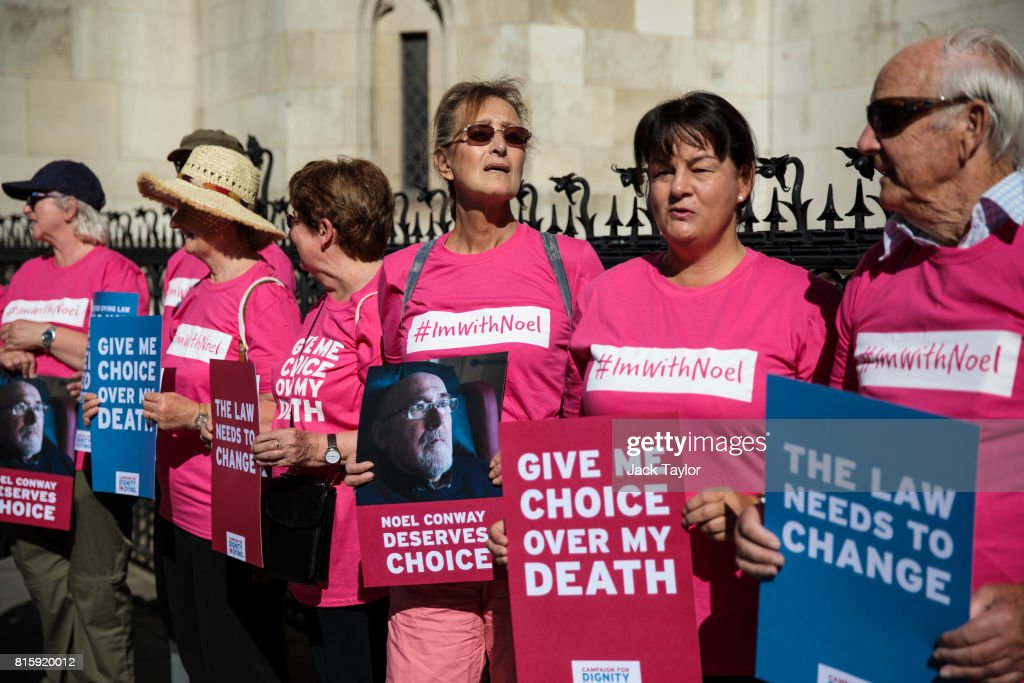 Supporters of Noel Conway from the campaign group Dignity in Dying stand with placards outside the Royal Courts of Justice, Strand on July 17, 2017 in London, England. Mr Conway, 67, who is terminally ill with motor neurone disease, is seeking a legal challenge on the law banning assisted dying.