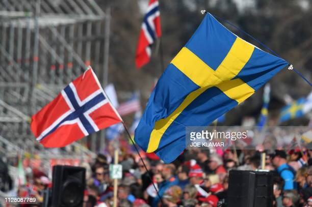 Supporters of Norway and Sweden wave national flags during the Ladies' cross country skiing relay 4x5km event at the FIS Nordic World Ski...