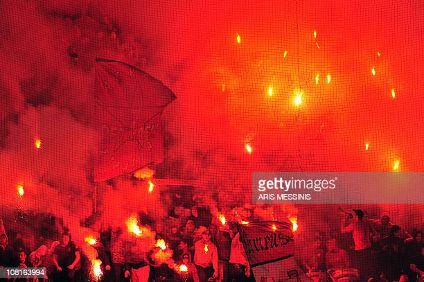Supporters of Olympiakos light flares and wave flags during a Greek Cup football match against PAOK at the Karaiskaki stadium in Athens on January...