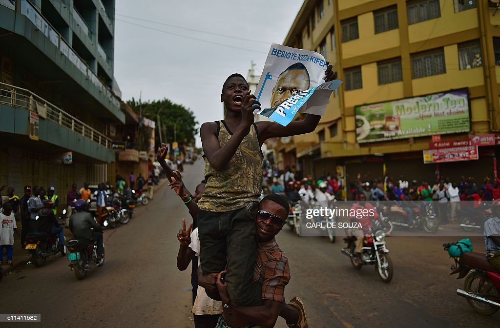 TOPSHOT - Supporters of opposition leader Kizza Besigye cheer for him despite the announcement that President Yoweri Museveni has won the presidential election for a fifth term in Kampala on February 20, 2016. Uganda's President Yoweri Museveni extended his three-decade rule, after winning a fifth term in polls rejected as fraudulent by the opposition leader under house arrest. The veteran 71-year-old won 60 percent of the vote in the sometimes chaotic elections, far ahead of the 35 percent garnered by detained opposition chief Kizza Besigye, whose house was surrounded by dozens of armed police in riot gear. / AFP / CARL