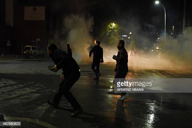 Supporters of opposition MP Albin Kurti kicks off a tear gas canister during clashes with Kosovo police in central Pristina on October 12 2015 Kurti...