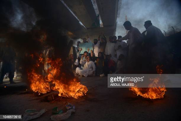 Supporters of opposition party Pakistan Muslim League Nawaz shout slogans as they burn tyres against the arrest of opposition leader Shahbaz Shrarif...