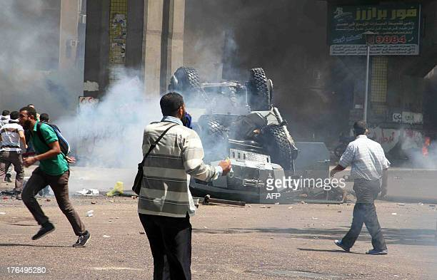 Supporters of ousted president Mohamed Morsi and members of the Muslim Brotherhood walk past police officers lying next to and on an overturned...