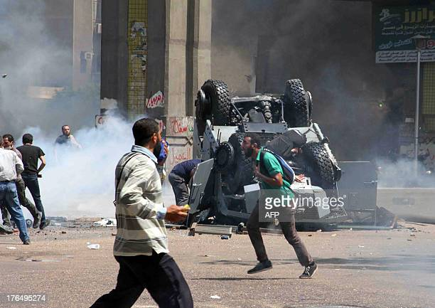 Supporters of ousted president Mohamed Morsi and members of the Muslim Brotherhood run past police officers lying next to and on an overturned...