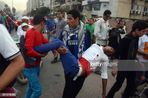 Supporters of ousted president Mohamed Morsi and the Muslim brotherhood carry an injured comrade during clashes with Egyptian riot police close to...