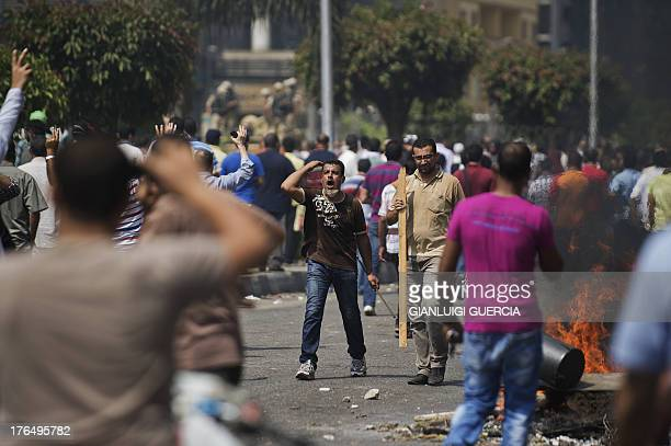 Supporters of ousted president Mohamed Morsi clash with Egyptian riot police on a street leading to Rabaa al-Adawiya square in Cairo on August 14,...