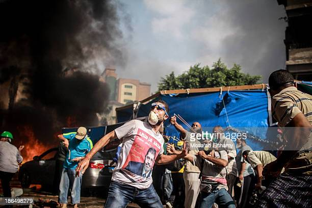 Supporters of ousted president Mohamed Morsi throw rocks at security forces during the violent dispersal of Rabaa Adaweya camp which left at least...