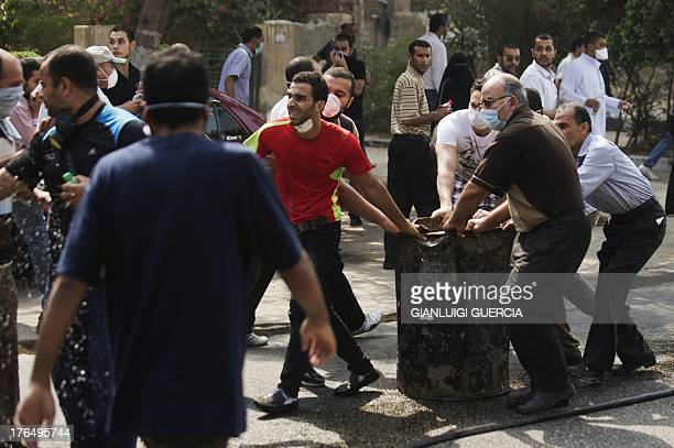 Supporters of ousted President Mohamed Morsi try to build a barricade as they clash with Egyptian riot police on a street leading to Rabaa al-Adawiya...