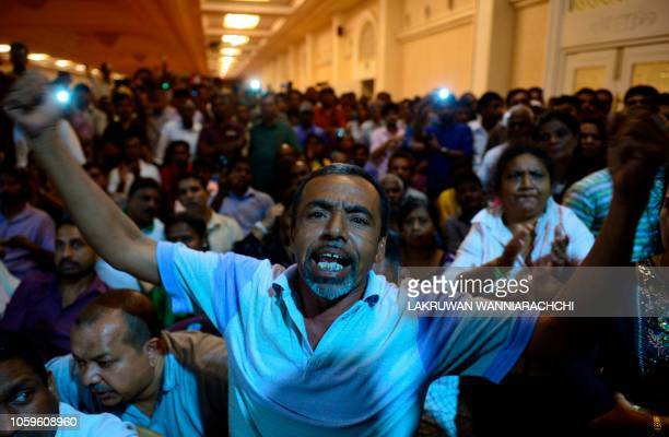 Supporters of ousted Sri Lanka's Prime Minister Ranil Wickremesinghe shout slogans as they gather at the prime minister's official residence in...