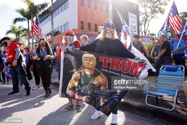 Supporters of outgoing US President Donald Trump await his return to Florida along the route leading to his Mar-a-Lago estate on January 20, 2021 in...