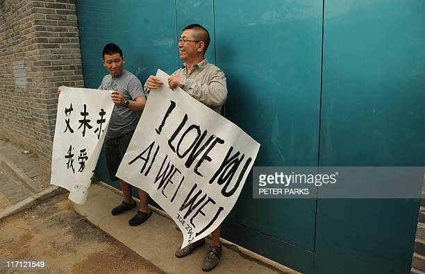 Supporters of outspoken Chinese artist Ai Weiwei arrive with banners saying i love you Ai Weiwei in English and Chinese at his studio in Beijing on...