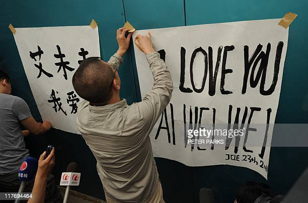Supporters of outspoken Chinese artist Ai Weiwei put up banners saying i love you Ai Weiwei in English and Chinese at his studio in Beijing on June...
