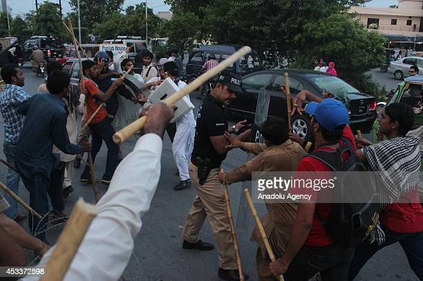 Supporters of Pakistan Awami Tehreek armed with sticks clash with Pakistani police near the Minhajul Quran Secretariat in Model Town Lahore on August...