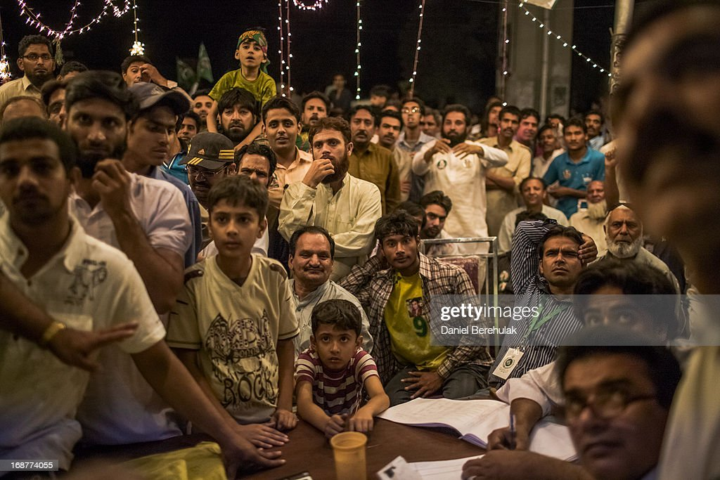 Supporters of Pakistan Muslim League-N (PMLN) watch intently as election results are announced on a television in front of a party office late evening on May 11, 2013 in Lahore, Pakistan. Millions of Pakistanis cast their votes in parliamentary elections held today on May 11. It is the first time in the country's history that an elected government will hand over power to another elected government.