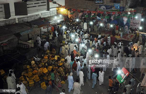 Supporters of Pakistan People's Party gather at the site where a bomb exploded during a PPP campaign meeting in Karachi on April 27 2013 Three bomb...