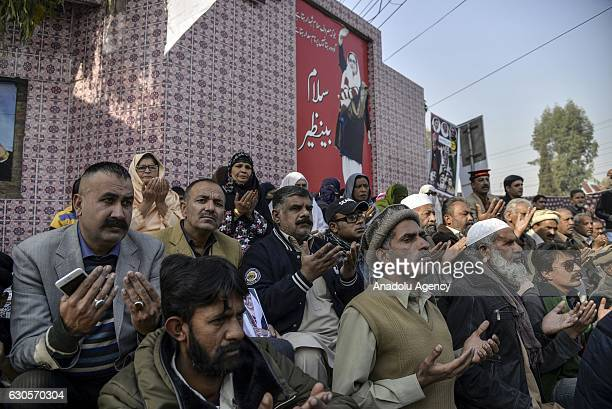 Supporters of Pakistan People's Party of former Prime Minister Benazir Bhutto pray with their hands raised during a prayer ceremony held for their...