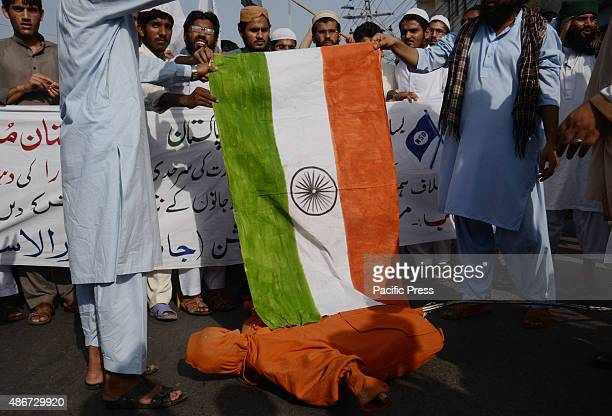 Supporters of Pakistan religious party Muslim Students Organization burning Indian flag and an effigy of Indian Prime Minister Narendra Modi to...
