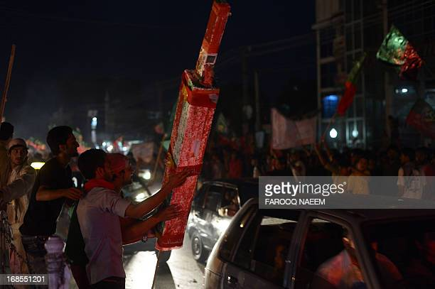 Supporters of Pakistan Tehreek-e-Insaf wave flags on the street in Rawalpindi on May 11, 2013. Millions of Pakistanis turned out to vote in landmark...