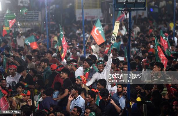 Supporters of Pakistani cricket star-turned-politician and head of the Pakistan Tehreek-e-Insaf Imran Khan wave party flags during a campaign meeting...